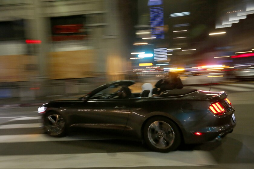 A motorist drives along Main Street in downtown Los Angeles despite a citywide curfew