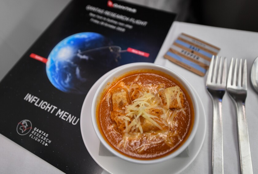 A bowl of spicy tomato soup surrounded by an in-flight menu, salt and pepper packet and silverware.