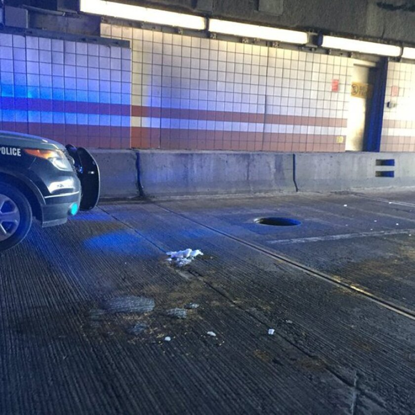 A police vehicle is parked in front of a manhole cover at the Thomas P. O'Neill Tunnel on Friday, Feb. 12, 2016 in Boston. The manhole cover that weighs more than 200 pounds killed a woman when it flew up in the air and crashed through her windshield as she drove on the Boston highway Friday morning, authorities said. (Steve Annear/The Boston Globe via AP) BOSTON HERALD OUT, QUINCY OUT; NO SALES; MANDATORY CREDIT