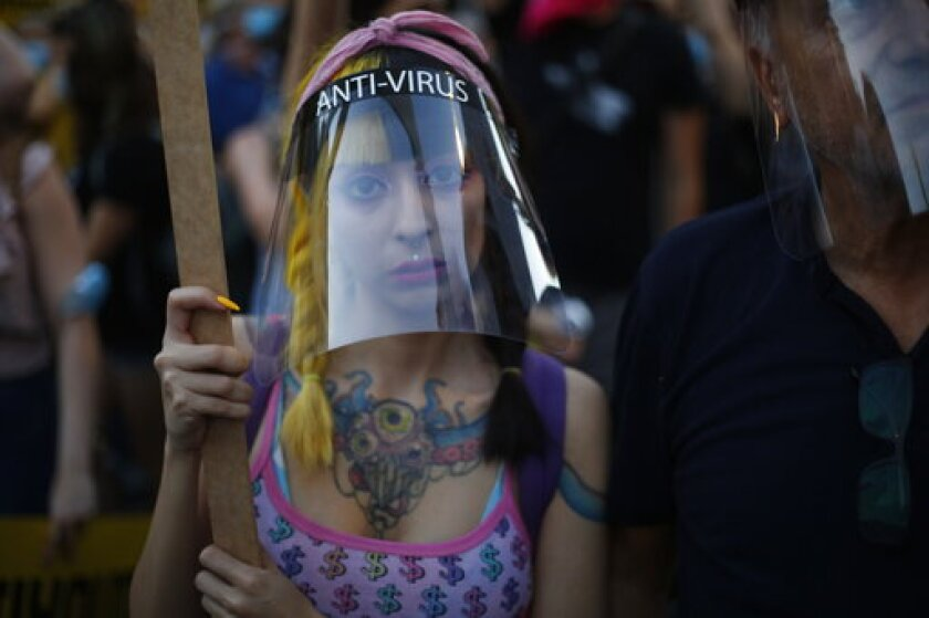 A protester wears a face mask to curb the spread of the coronavirus outside of the Prime Minister's residence in Jerusalem, Tuesday, July 14, 2020. Thousands of Israelis demonstrated outside the official residence of Benjamin Netanyahu, calling on the embattled Israeli leader to resign as he faces a trial on corruption charges and grapples with a deepening coronavirus crisis. (AP Photo/Ariel Schalit)