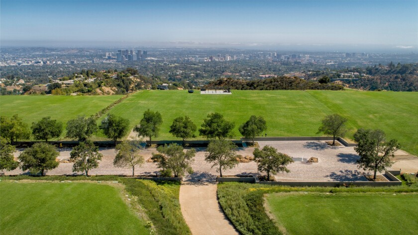 Aerial view of green grass and trees on an undeveloped plot of land on a hilltop overlooking the Los Angeles Basin