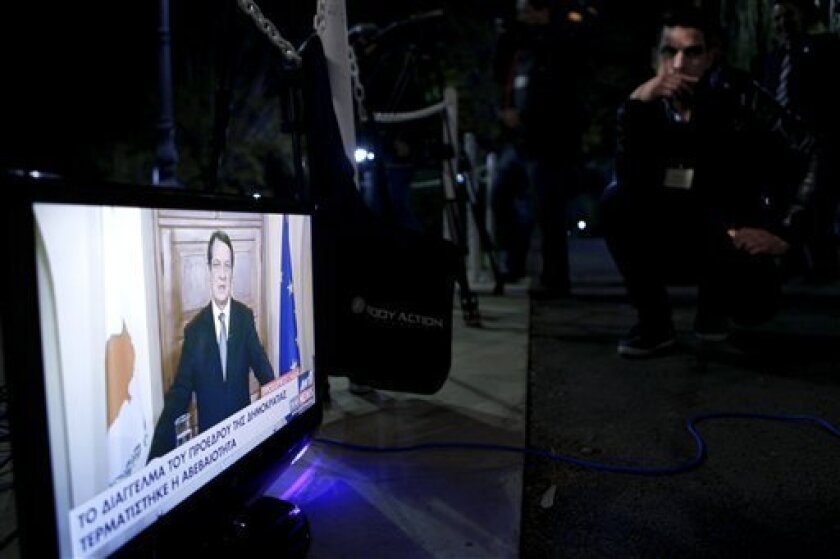 A TV channel employee watch the Cyprus' President Nicos Anastasiades speaks during a live, televised address to the nation from the Presidential Palace in the capital Nicosia, Cyprus, Monday, March 25, 2013. A deal to provide Cyprus with an international bailout was clinched in the early hours of M
