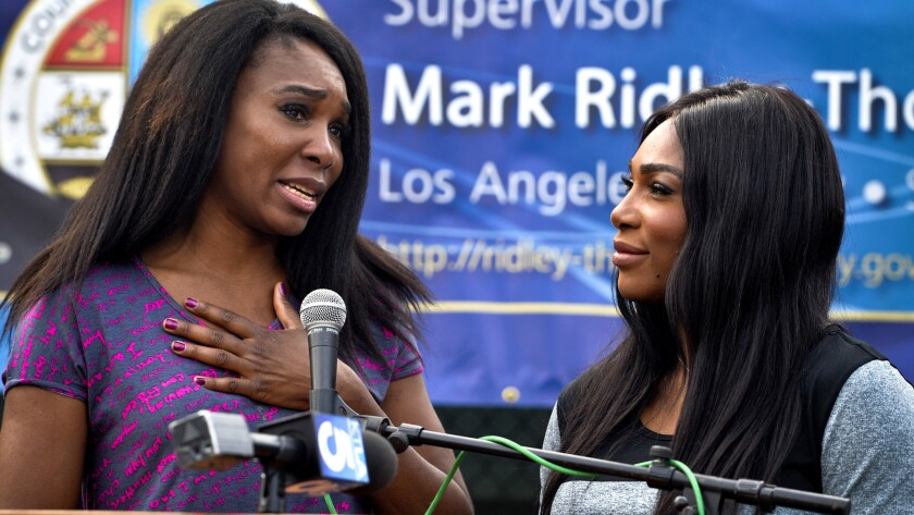 Sisters Venus, left, and Serena Williams speak at the opening ceremony for new tennis courts at East Rancho Dominguez County Park in Compton on Saturday.