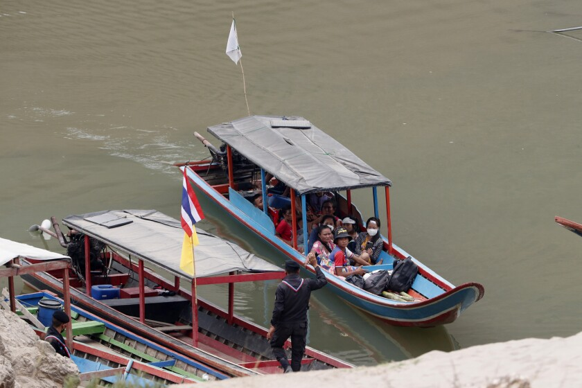 FILE - In this March 30, 2021, file photo, Karenni villagers from Myanmar arrive on a boat with an injured person as they evacuate to Ban Mae Sam Laep Health Center in Mae Hong Son province, northern Thailand. Far away in Myanmar's borderlands, millions of others who hail from Myanmar's minority ethnic groups are facing increasing uncertainty and waning security as longstanding conflicts between the military and minority guerrilla armies flare anew. (AP Photo/Sakchai Lalit, File)