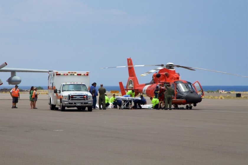 In this photo provided by the U.S. Coast Guard, Coast Guard crews safely deliver David McMahon and Sidney Uemoto to emergency medical personnel in Kona, Hawaii, Friday, July 15, 2016, following their rescue nine miles off Kona. They were both rescued by a Coast Guard MH-65 Dolphin helicopter crew following an expansive joint search by Navy, Royal New Zealand air force, U.S. Air Force and Coast Guard crews. They reportedly sustained only minor injuries in the crash. (Kevin Cooper/U.S. Coast Guard via AP)