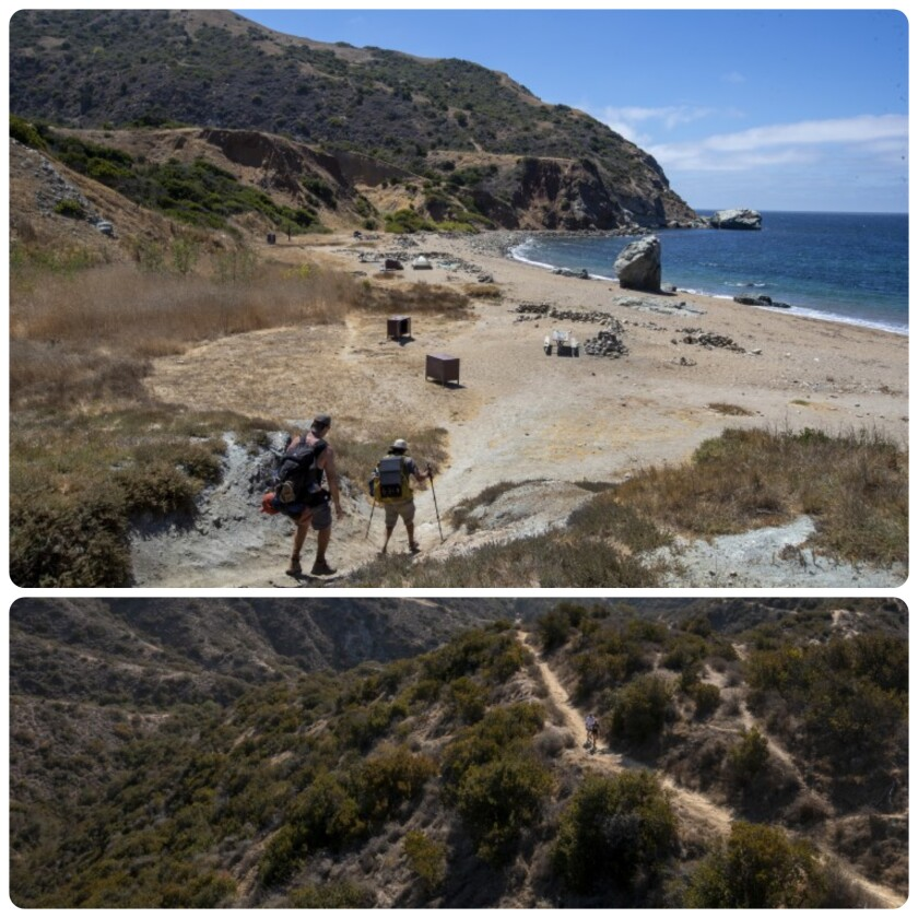 Hikers approach a small, sandy beach and a inland hiking trail.
