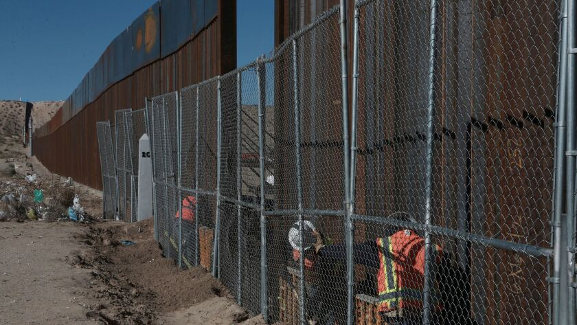 Workers this month extend the height of the border fence separating the towns of Anapra, Mexico, and Sunland Park, New Mexico.