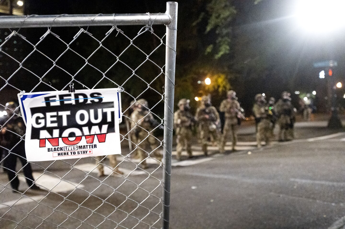 Federal agents disperse Black Lives Matter protesters near the Mark O. Hatfield United States Courthouse on Monday, July 20, 2020, in Portland, Ore. Officers used teargas and projectiles to move the crowd after some protesters tore down a fence fronting the courthouse. (AP Photo/Noah Berger)