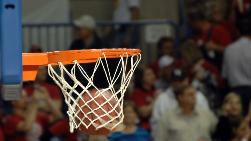 Basketball swooshes through a basketball hoop during a basketball game. Crowd shows in the backgrou