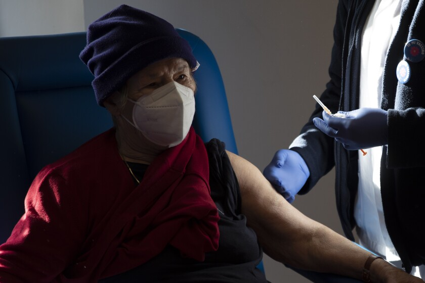 A medical staff member prepares to administer a dose of the Pfizer-Biotech vaccine to an over eighty-year-old, in the Santa Maria della Pieta hospital in Rome, Monday, Feb. 8, 2021. (AP Photo/Alessandra Tarantino)