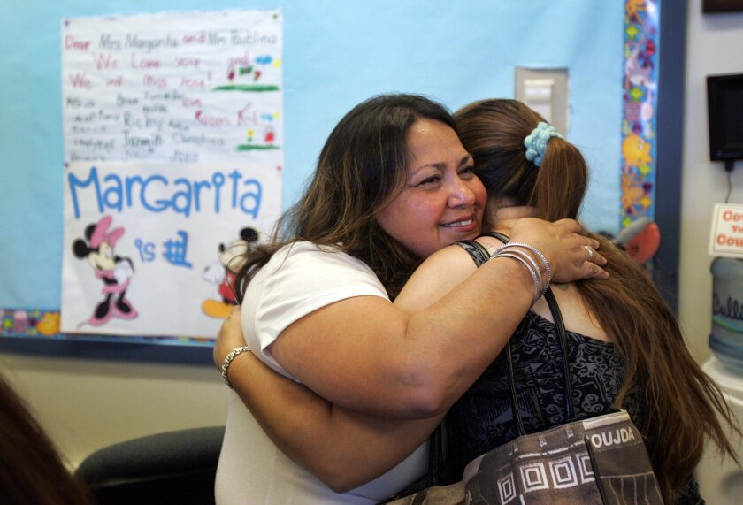 "As school clerk Margarita Lopez prepared to leave Audubon Elementary school after 25 years on Thursday, she gets a hug from Lori Ramos, a student's parent. Ramos was involuntarily transferred to Mission Bay High school as part of a ""bumping"" process that shifts around remaining employees following layoffs."