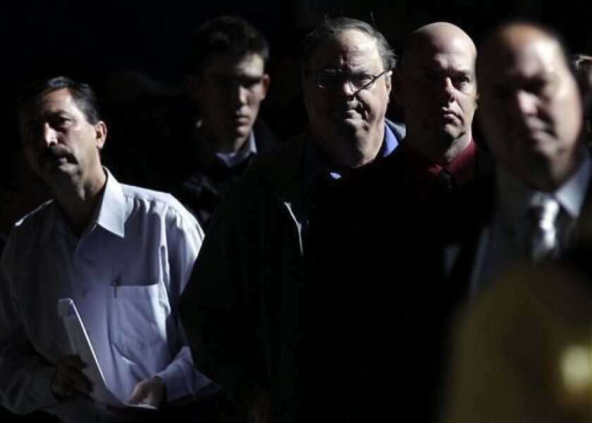 FILE - In this Nov. 30, 2010 file photo, Mark Chavez, second from right, waits in a line to register at a career fair in San Diego. Job openings dipped in November, the latest evidence that employers remain cautious about adding new workers.(AP Photo/Gregory Bull, File)