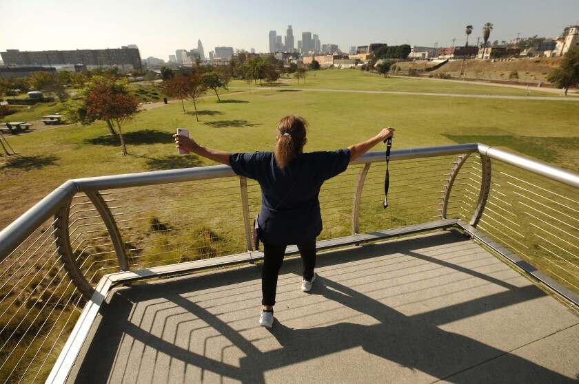 Xochitl Manzanilla stands on the pedestrian bridge overlooking Los Angeles State Historic Park