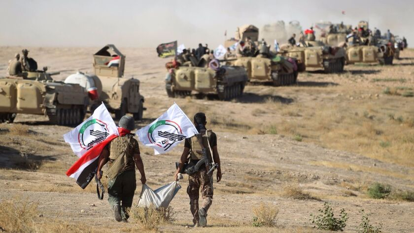 Fighters from Popular Mobilization forces advance toward the town of Tall Afar, west of Mosul, after the Iraqi government announced the beginning of the operation to retake it from the control of Islamic State group on Aug. 22, 2017.