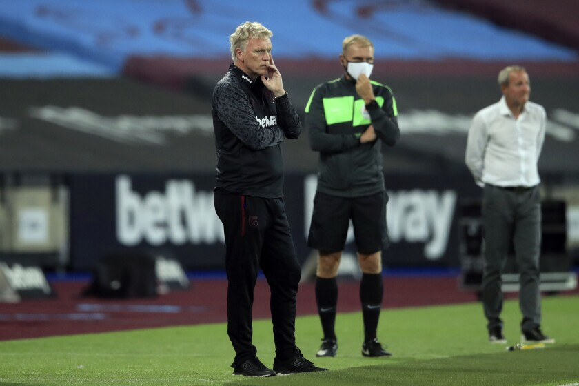 West Ham's manager David Moyes, left, and Charlton Athletic's manager Lee Bowyer, right, stand by the touchline during the English League Cup soccer match between West Ham United and Charlton Athletic at London stadium in London, Tuesday, Sept. 15, 2020. (Adam Davy/Pool via AP)