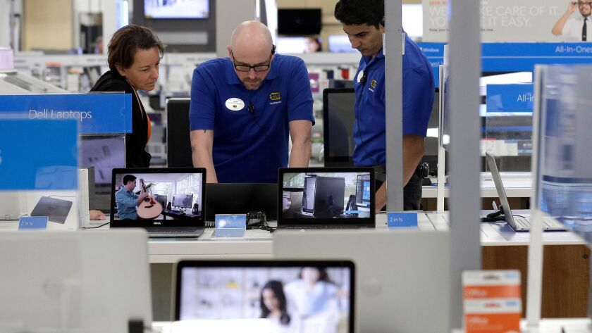 In this May 23 photo, employees assist a customer at Best Buy in Cary, N.C.