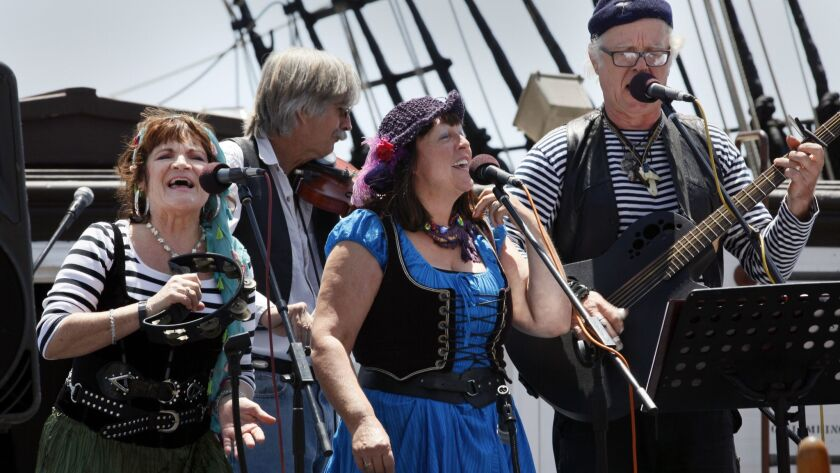 Jeanne Reith, left, Floyd Fronius, Jean Stewart and Mike Stewart of the group Raggle Taggle, perform a sea chantey about pulling along behind the ship after drinking a bit too much, during the annual Sea Chantey Festival at the San Diego Maritime Museum.