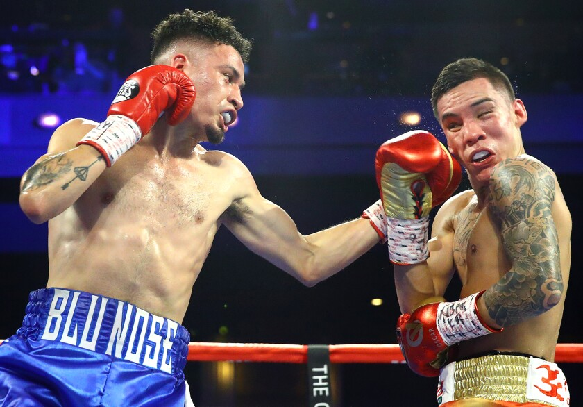 Adam Lopez, left, punches Oscar Valdez during their junior lightweight fight at the Cosmopolitan in Las Vegas on Nov. 30, 2019.