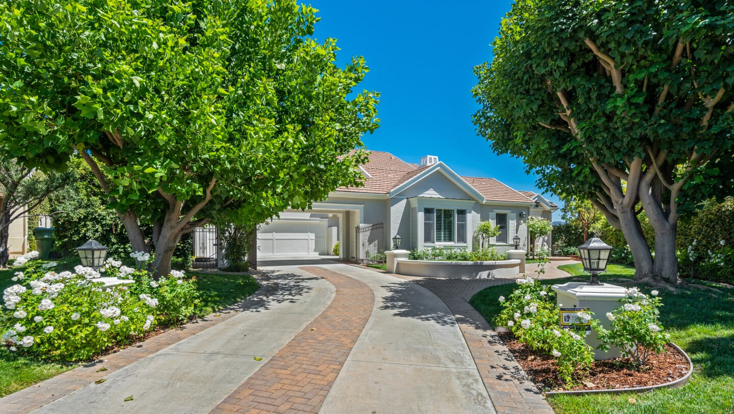 The estate spans half an acre in the guard-gated Oaks of Calabasas neighborhood and centers on a 6,000-square-foot custom home.