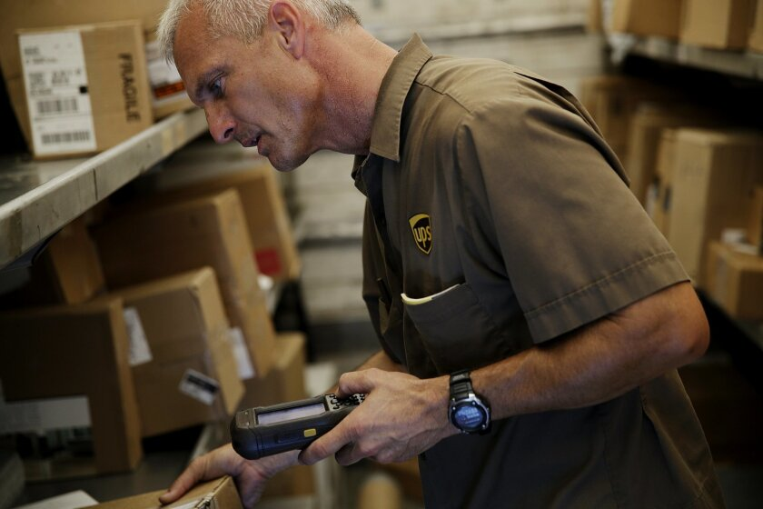 In this June 20, 2014 photo, United Parcel Service (UPS) driver Marty Thompson scans a package before a delivery in Cumming, Ga. UPS reports quarterly financial results on Tuesday, July 28, 2015. (AP Photo/David Goldman)