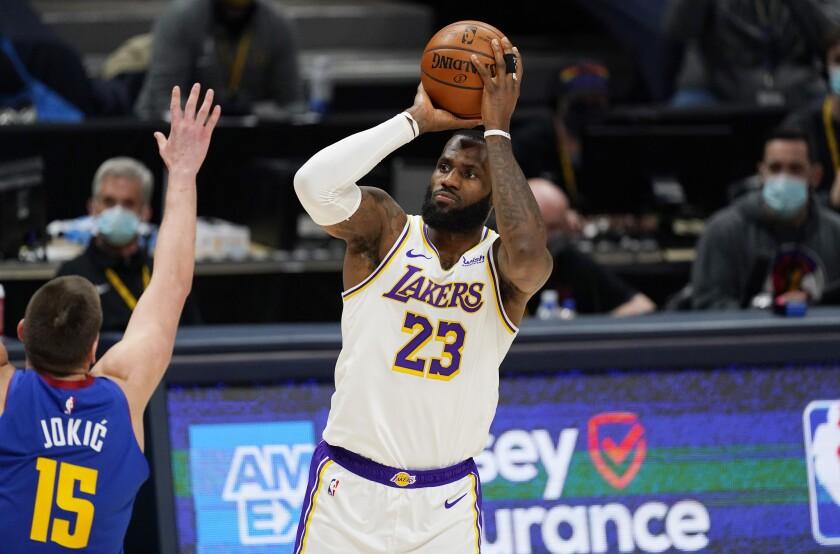 LeBron James shoots over Denver Nuggets center Nikola Jokic.