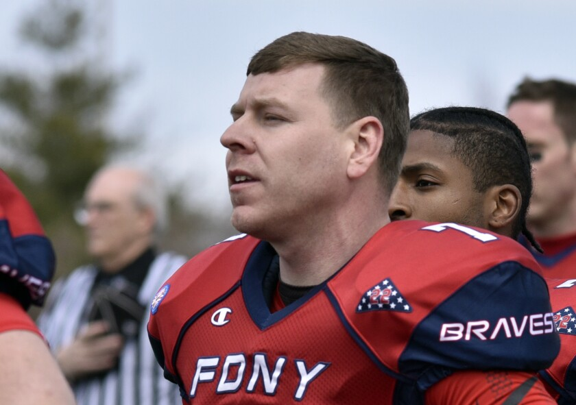 FDNY Bravest Quarterback Daniel Woodford (7) stands for the National Anthem before playing the Philadelphia Blue Flame in a tackle football game Saturday, April 7, 2018 at Petrides High school.