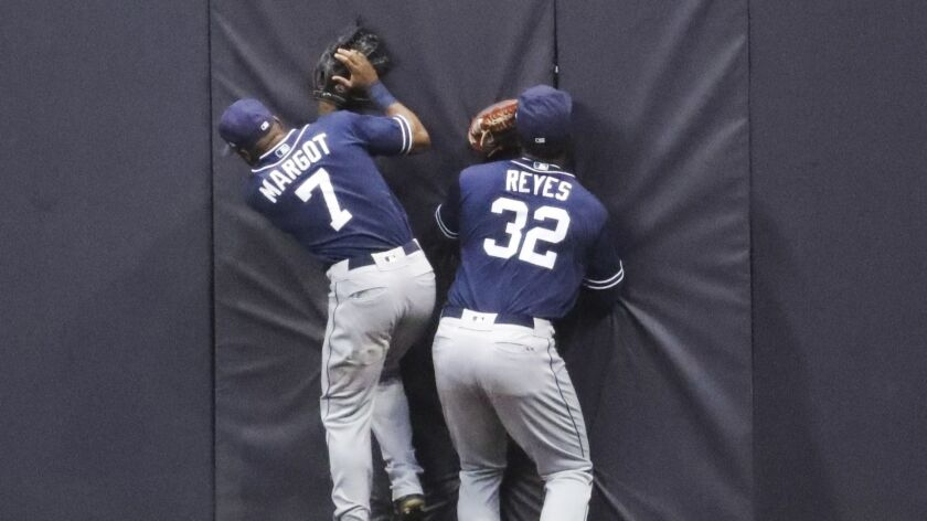 Manuel Margot (7) and Franmil Reyes (32) run into the wall after Reyes catches a fly ball hit by the Brewers' Ryan Braun in the third inning Tuesday.