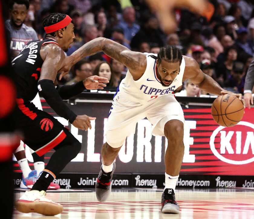 Clippers forward Kawhi Leonard drives to basket against Raptors forwartd Rondae Hollis-Jefferson during a game Nov. 11 at Staples Center.