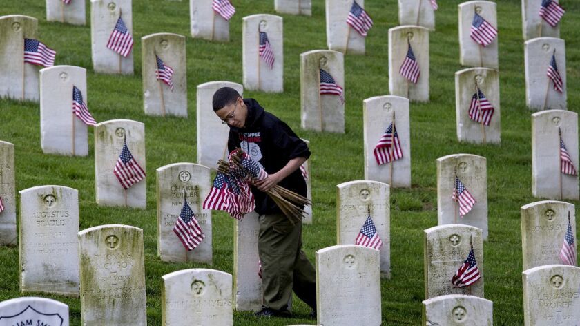 Boy Scout Daniel Perez, 11, of New York, places American Flags on graves at Cypress Hills National Cemetery in Brooklyn.