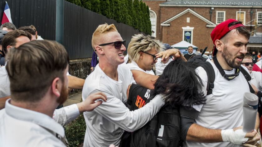 Benjamin Drake Daley, center, attacks an unidentified woman on Aug. 12, 2017, in Charlottesville, Va., while Cole Evan White, at left, looks on. At right is Michael Paul Miselis of Lawndale.