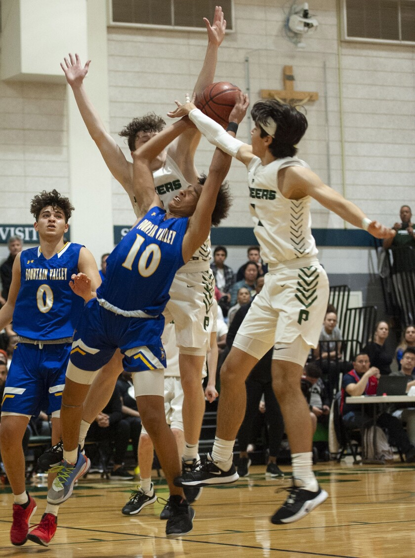 Fountain Valley's Roddie Anderson gets the would while under pressure from Providence's Jordan Shelley, left, and Providence's Michael Joanou during CIF State Division III Southern California Regional semifinal at Providence High. (Photo by Miguel Vasconcellos)