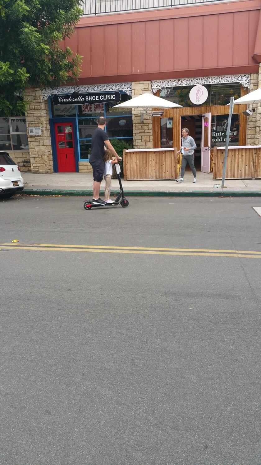 This adult and child are seen in La Jolla breaking two California Vehicle Codes: The operator of a scooter cannot have any passengers, and riders under the age of 18 must wear a helmet.