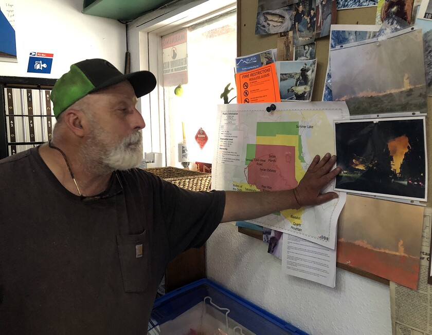 Dale Chiono surveying photos of past wildfires posted in his store.