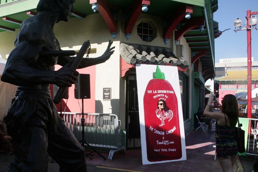Sriracha lovers took pictures with their favorite hot sauce near a statue of Bruce Lee in Chinatown.