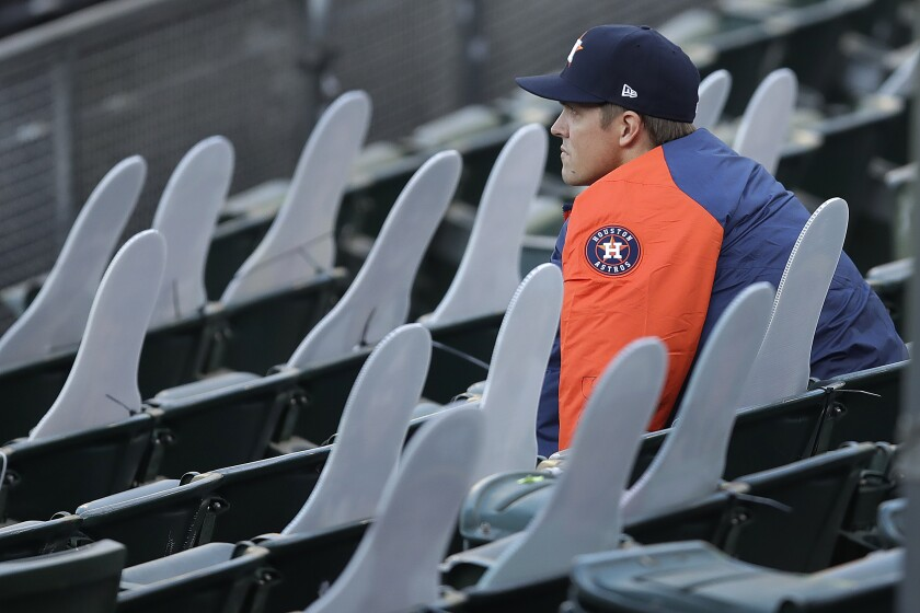El pitcher de los Astros de Houston Zack Greinke sentado tras las figuras de cartón de aficionados que ocupan la grada del Oakland Coliseum en el cuarto inning del juego de la MLB que enfrentó a su equipo con los Atléticos de Oakland, el 7 de agosto de 2020, en Oakland, California. (AP Foto/Ben Margot)