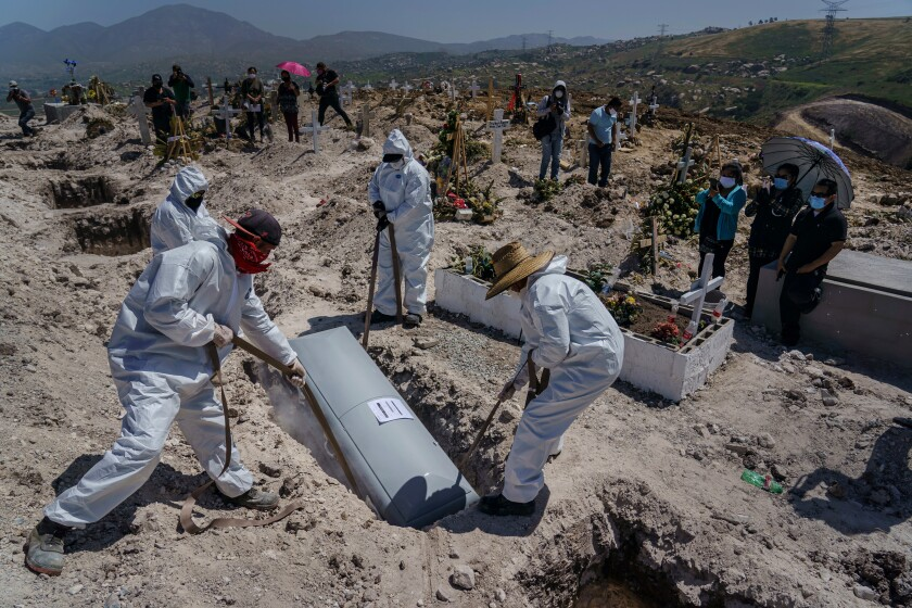 Cemetery workers lower the casket of Juan Velasco, who died with COVID-19 symptoms, April 27 at a cemetery in Tijuana.