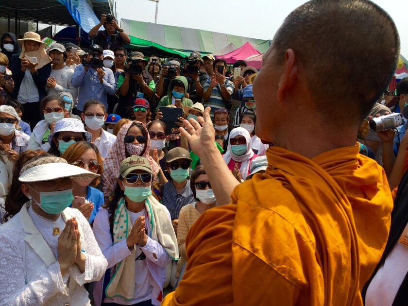 Hands clasped in prayer, followers of the Buddhist Dhammakaya sect meet with a monk outside their temple north of Bangkok, where their spiritual leader is believed to be evading arrest.