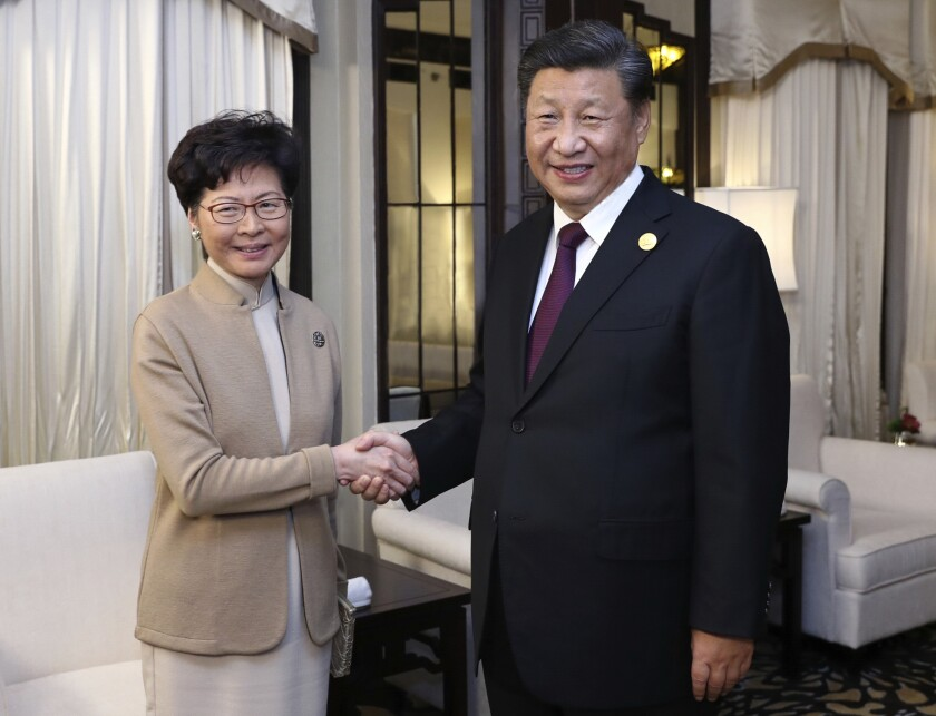 FILE - In this Nov. 4, 2019, file photo released by China's Xinhua News Agency, Chinese President Xi Jinping, right, poses with Hong Kong Chief Executive Carrie Lam for a photo during a meeting in Shanghai, China. A sharp escalation of violence in Hong Kong has once again raised the question of how China's central government will respond. Experts said national security measures and deployment of the armed forces remain possibilities, though Beijing may just as likely allow destruction to continue unfolding. (Ju Peng/Xinhua via AP, File)