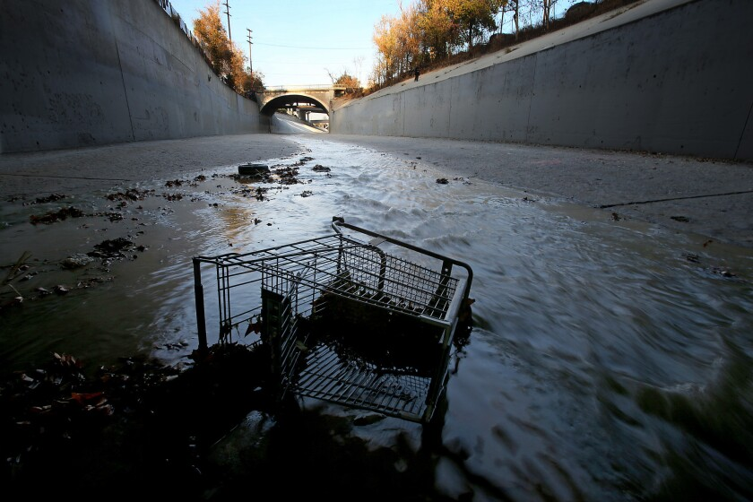 A grocery cart lies in the stream of the Arroyo Seco at its confluence with the Los Angeles River north of downtown. Plans to revitalize the long neglected L.A. River corridor includes $6 billion in real estate investment.