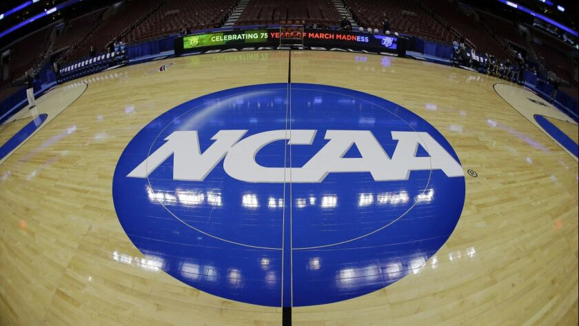 FILE - In this March 21, 2013, file photo, taken with a fisheye lens, the NCAA logo is displayed on