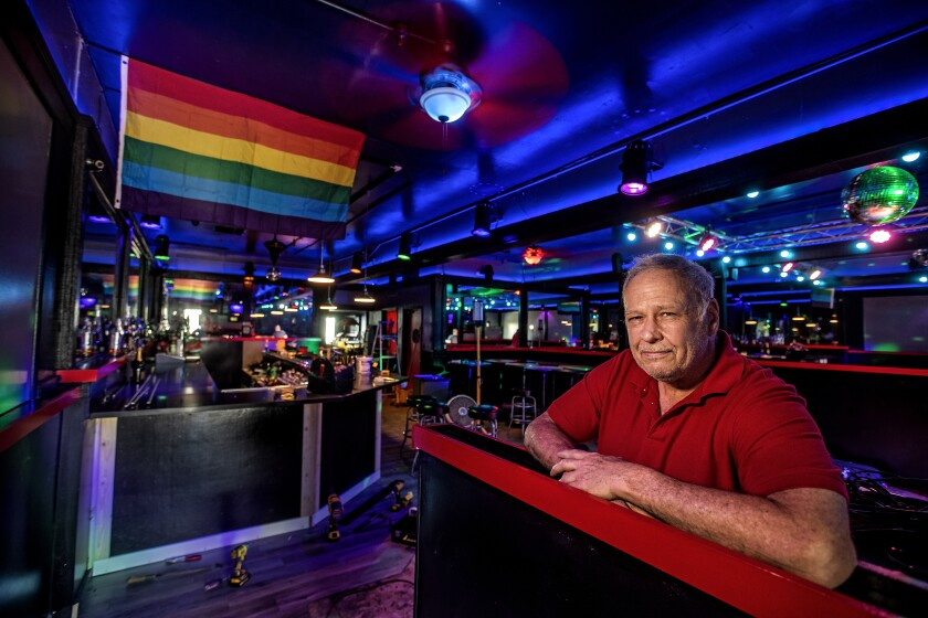 Steve Terradot inside his bar, the Boulevard, bathed in blue lights with a Pride flag on the wall.