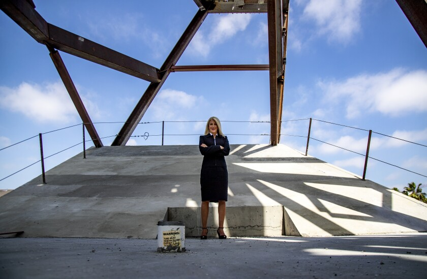 A blond woman in a business suit stands with arms crossed at the Orange County Museum of Art construction site.