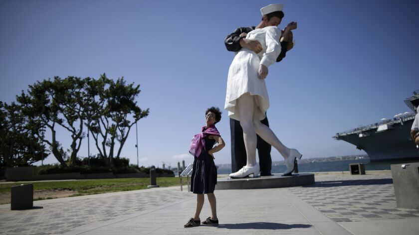 "A tourist from China stands in front of the sculpture ""Unconditional Surrender"" in San Diego on Sept. 18, 2015."