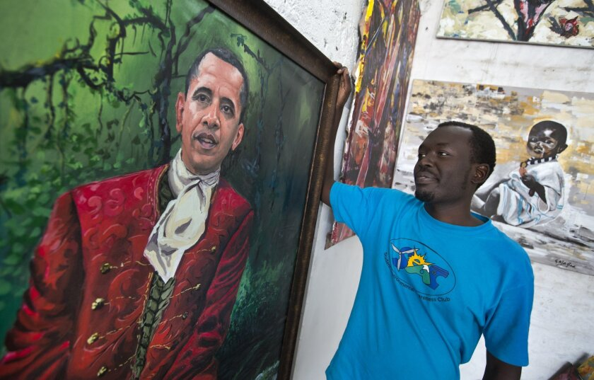 "Kenyan artist Evans Yegon, known as ""Yegonizer"", poses by one of two paintings of President Barack Obama that he has completed in recent weeks, at his studio in the GoDown Arts Centre in Nairobi, Kenya Wednesday, July 22, 2015. In his first trip to Kenya since he was a U.S. senator in 2006, Obama is scheduled to arrive in Kenya on Friday, the first stop on his two-nation African tour in which he will also visit Ethiopia. (AP Photo/Ben Curtis)"