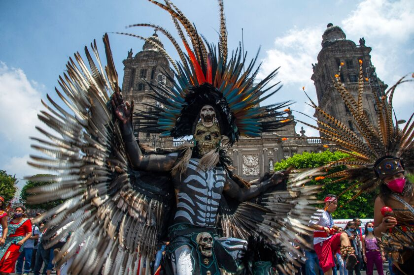A person in skeleton costume and mask and a headdress adorned with plumes displays feathered wings