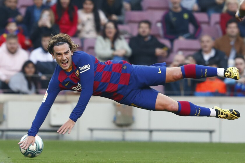 FILE - In this file photo dated Saturday Feb. 22, 2020, Barcelona's Antoine Griezmann falls during a Spanish La Liga soccer match against Eibar at the Camp Nou stadium in Barcelona, Spain. Griezmann arrived to Camp Nou last summer with the task of completing an intimidating strike trio with Messi and Suárez, but one year later, the French world champion can barely get on the pitch, and was left out of Barcelona's starting 11 on Tuesday June 30, 2020. (AP Photo/Joan Monfort, FILE)