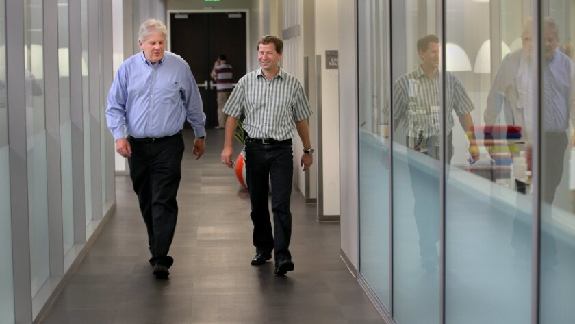 Eli Lilly is doubling the size of its research center in La Jolla. Thomas Bumol, left, the director of Lilly Biotechnology Center, walks the halls of the present laboratory complex with Wolfgang Glaesner, Chief Scientific Officer of the Lilly Biotech Group on Wednesday.