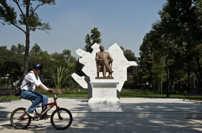 A man rides a bike in Mexico City in front of a sculpture of Heydar Aliyev, former president of Azerbaijan.