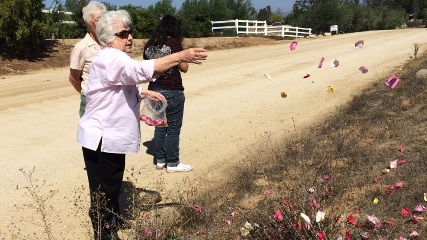 "Clara Trevino scatters rose petals in front of the property where her disabled nephew, Miguel Ferreyra ,was found dead. ""I just think about how they felt trying to get out and nobody was there to help them,"" Trevino said."