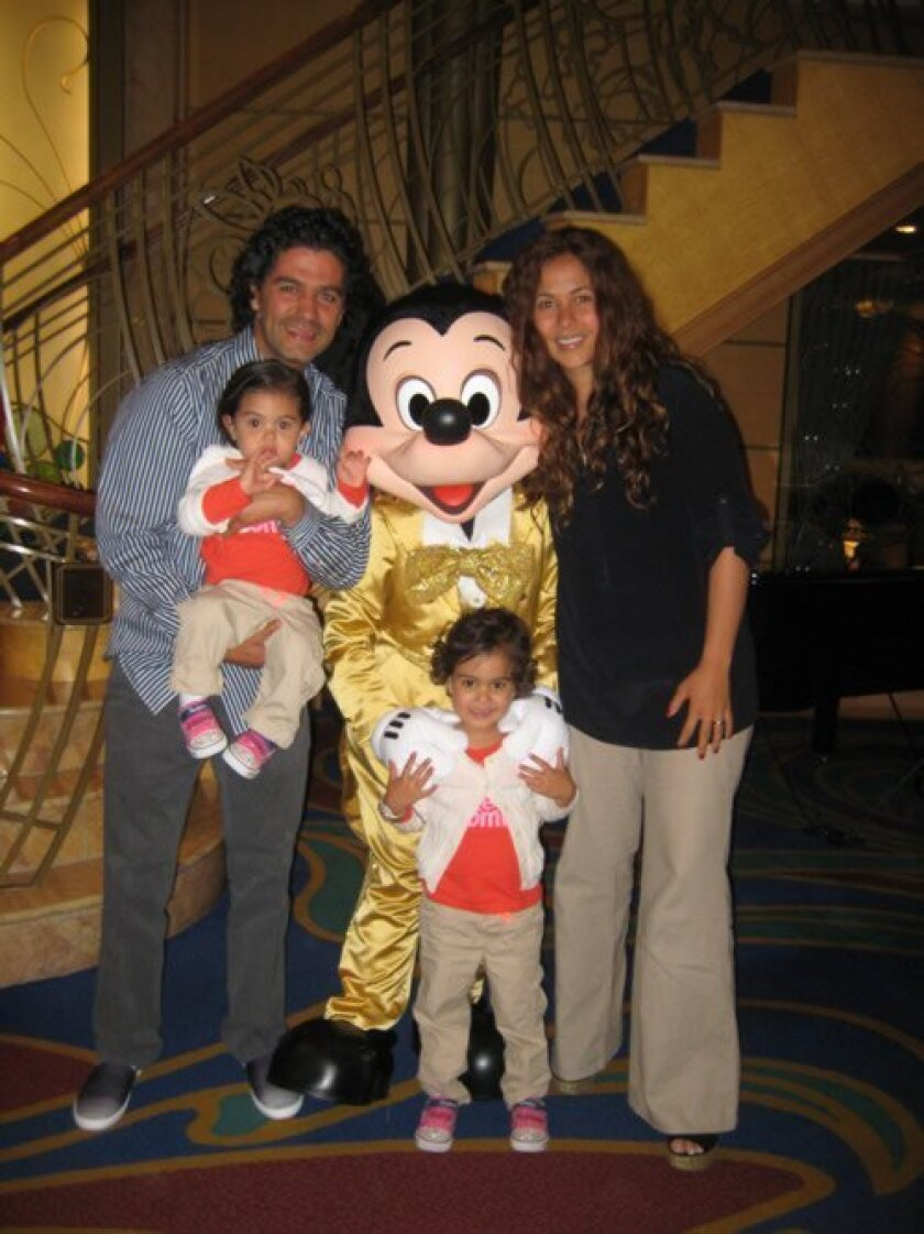 The Sahagun-Gonzales family — Santiago, Ivanna, Alé and Alejandra — meet Mickey Mouse during a Make-A-Wish Disney cruise. Courtesy